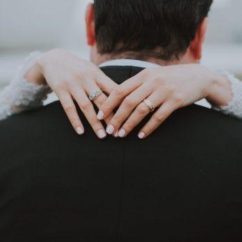 woman's hands around mans neck