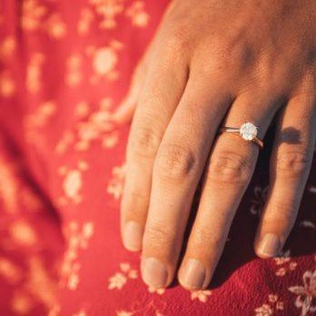 woman's hand wearing diamond engagement ring