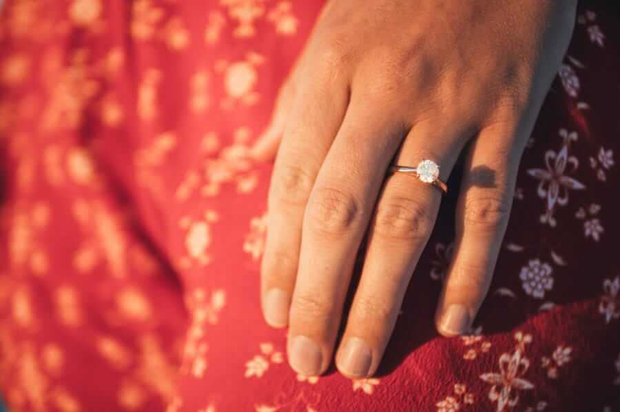 woman's hand wearing diamond engagement ring