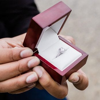 man holding box with engagement ring inside