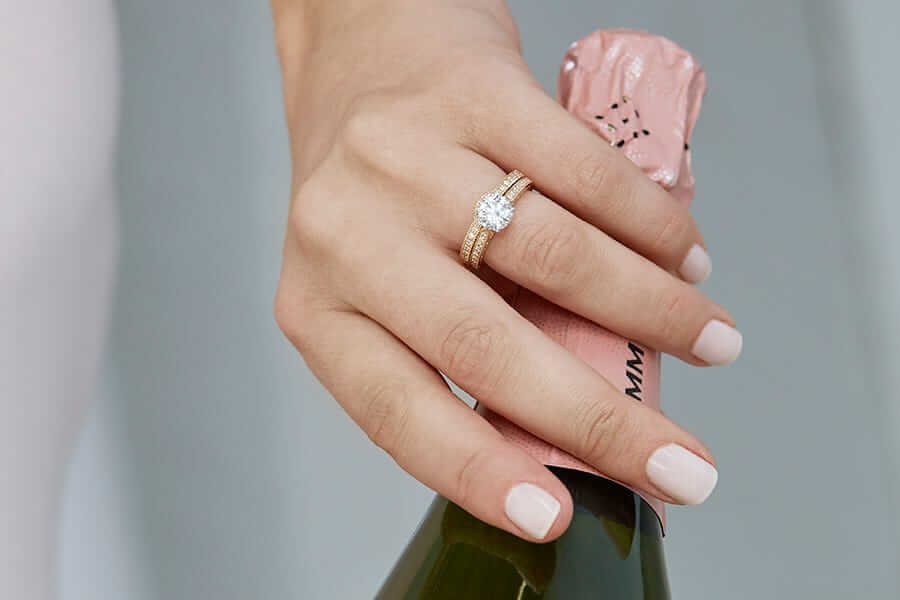 a hand holding a champagne bottle, wearing a wedding ring