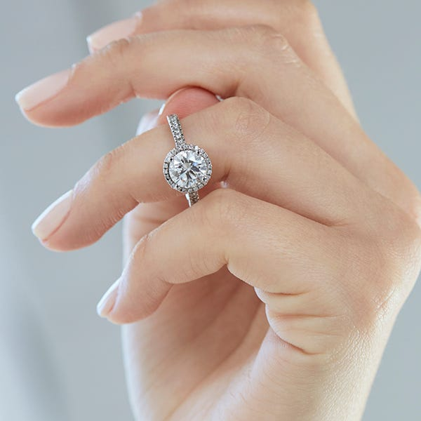 a hand wearing a white gold round halo engagement ring