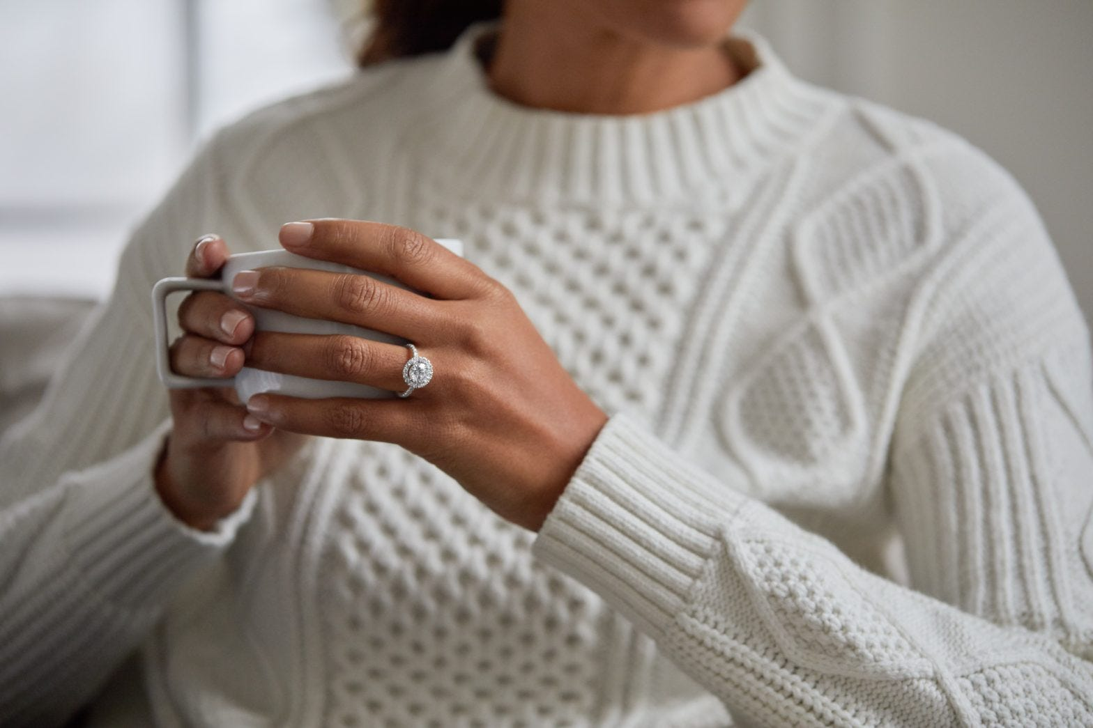 woman holding hot chocolate with engagement ring on