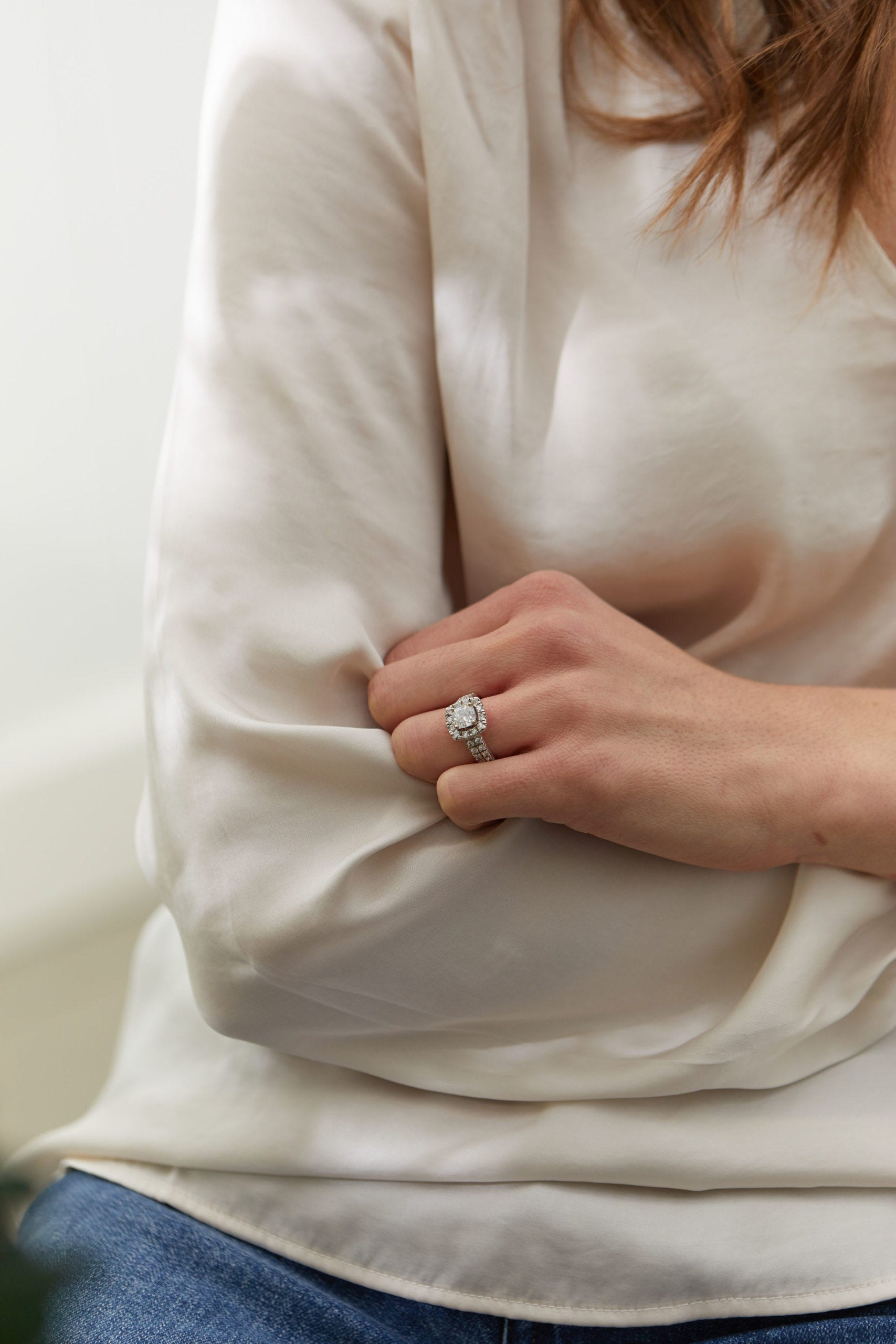 Woman wearing halo style engagment ring on hand