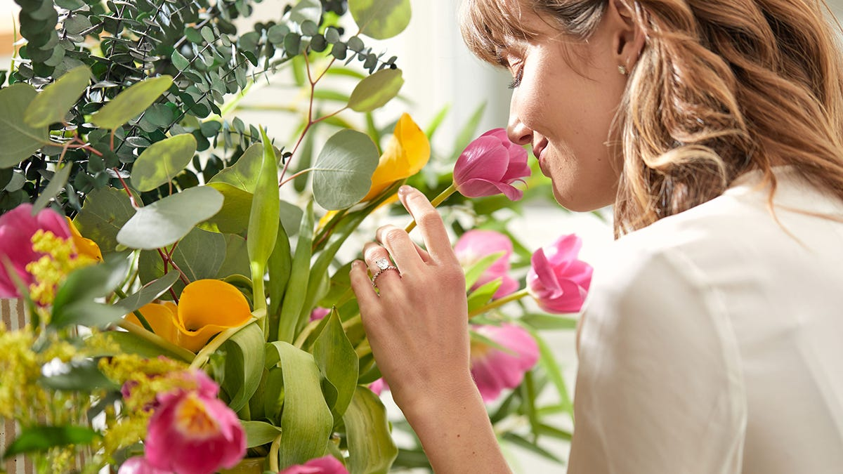 woman smelling tulip with engagement ring on