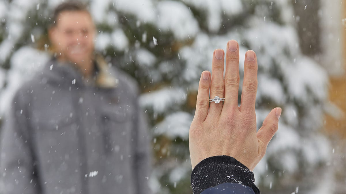 man smiling at woman wearing engagement ring in the snow