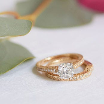 yellow gold engagment ring and wedding ring next to flowers and leaves