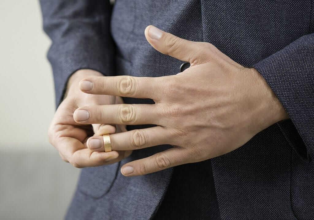 Man wearing yellow gold men's wedding ring