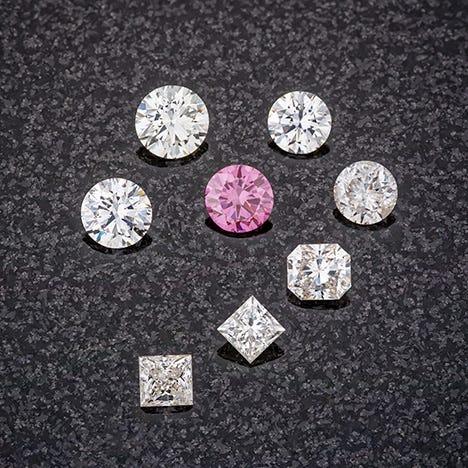 An array of colorless diamonds around a purple diamond.