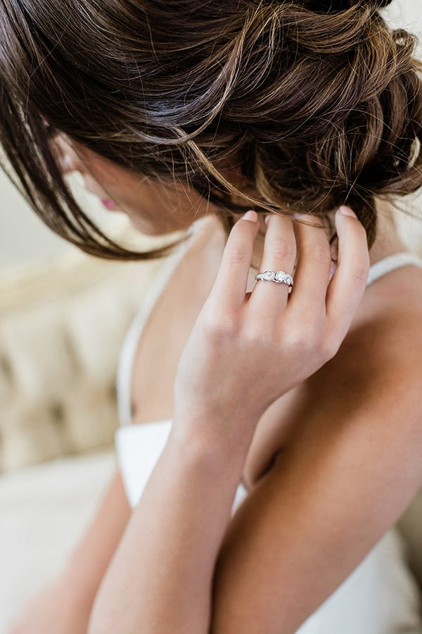 woman wearing art deco engagement ring and touching hair