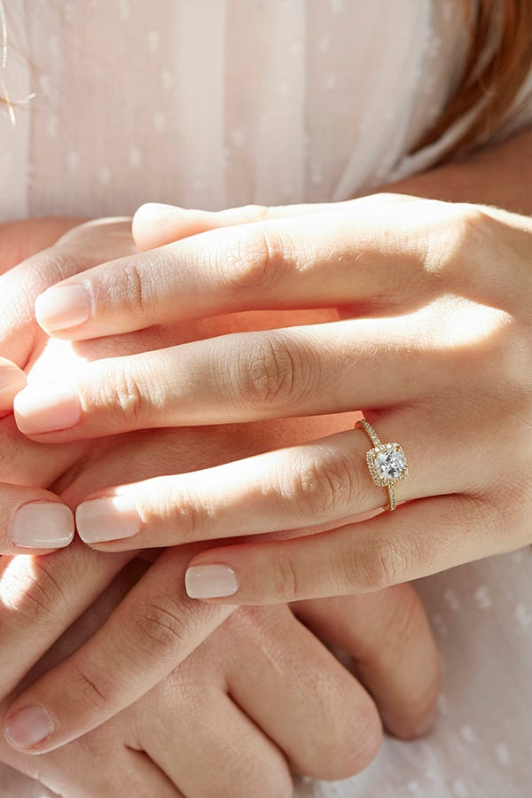 woman wearing cushion engagement ring