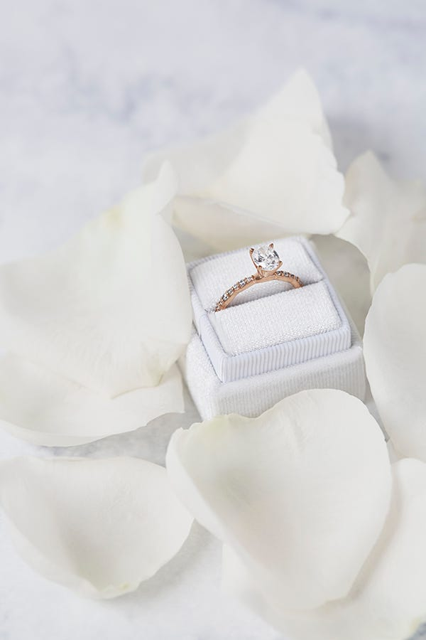 oval man made diamond ring in white ring box