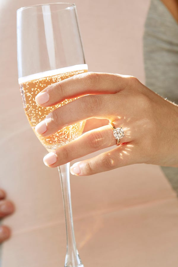 woman holding champagne glass wearing solitaire diamond ring