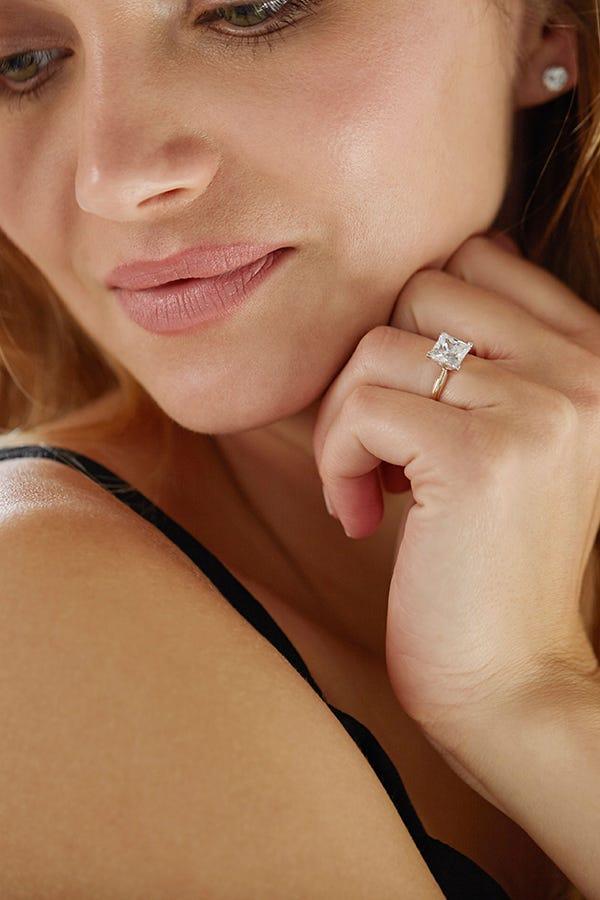 woman wearing princess shaped engagement ring